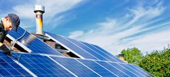 Pracovník inštaluje solárny fotovoltaický článok na strechu budovy